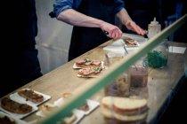 Man preparing sandwiches on kitchen counter — Stock Photo