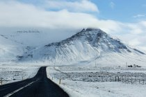 Snow covered mountains landscape with asphalt road — Stock Photo