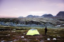 Person standing at tent in meadow in mountains — Stock Photo