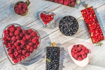 Raspberries and blueberries in bowls — Stock Photo
