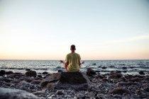 Vista de pessoa meditando na praia rochosa no mar traseira — Fotografia de Stock