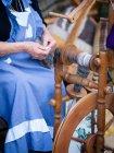 Senior woman working at vintage spinning-machine — Stock Photo