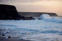 Waves breaking at rocky coastline — Stock Photo
