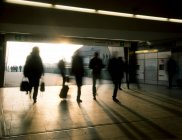 People silhouettes walking in underground tunnel — Stock Photo
