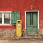 Old building facade with green wooden door and yellow petrol pump — Stock Photo