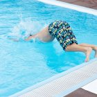 Boy jumping in swimming pool blue water — Stock Photo
