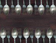 Wooden surface with vintage spoons and forks — Stock Photo