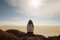 Back view of woman sitting on rocks and looking at desert with shining sun — Stock Photo