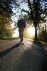 Особи, їзда скейтборд в парку на заході сонця — стокове фото