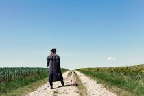 Man with dog outdoors on country road by the fields — Stock Photo