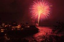 Cielo notturno con fuochi d'artificio rossi al city — Foto stock