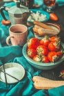 Kitchen table with blue bowl, strawberries and coffee — Stock Photo