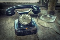 Blue old fashioned telephone with rotary dial on table with glass ashtray — Stock Photo
