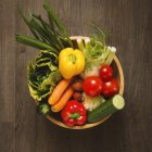 Top view of different vegetables in wicker wooden basin — Stock Photo