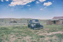 Ghost town with old vintage broken car and wooden hut — Stock Photo
