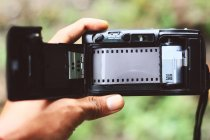 Hand holding open analog camera with film inside — Stock Photo