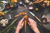 Людина пілінг морква — стокове фото
