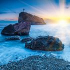 Seacoast at sunset and cross on a rock — стокове фото