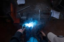 Welder at work by the table, overhead view — Stock Photo