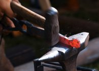 Close-up view of blacksmith forging iron on anvil — Stock Photo