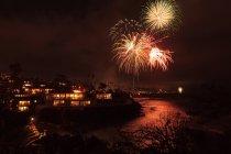 Cielo notturno con fuochi d'artificio sopra mare e città — Foto stock