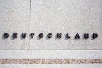 Calligraphic advertising, lettering headline mode on white building facade — Stock Photo