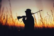 Hunter holding shotgun on shoulder and observing land — Stock Photo