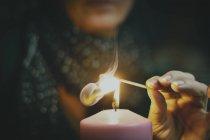 Vista potata della mano di persona che tiene candlewick sopra fuoco — Foto stock