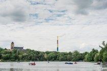 Tuyau coloré au bord du lac avec pédalos, entourée d'arbres — Photo de stock