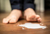 Recadrée vue des pieds de la personne avec le lait renversé sur le plancher — Photo de stock