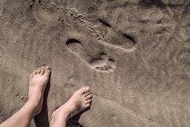 Regardant vers le bas de la vue de pieds nus et empreintes sur sable — Photo de stock