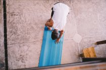 Rear view of man picking up yoga mat — Stock Photo