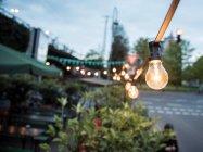 Girlande aus leuchtenden Lampen als Dekoration im Straßencafé — Stockfoto
