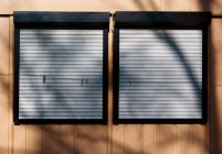 Empty clothesline with clothes pegs and closed shutters — Stock Photo