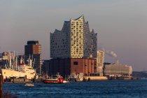 Cargo ships by Elbe philharmonic hall at sunset, Hamburg, Germany — Stock Photo