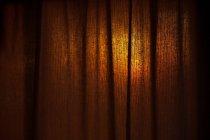 Braunen Vorhang mit Sonnenuntergang beleuchtet — Stockfoto