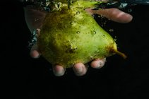 Human hand holding pear underwater — Stock Photo
