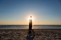 Person, die auf Kopf auf sandigen Strand bei Sonnenuntergang, Yoga-Konzept — Stockfoto