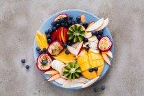 Tagliata di frutta con le bacche su piastra — Foto stock
