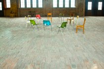 Circle of colorful empty chairs in spacious room — Stock Photo