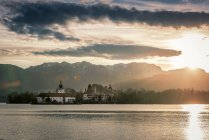 Escénica puesta de sol sobre lago con edificio de la iglesia - foto de stock