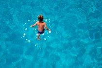 Заднього вигляду молодий хлопчик, купання в басейні — стокове фото
