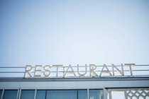 Restaurant signage at building rooftop against sky — Stock Photo