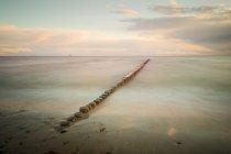 Bord de mer et de la rangée de poteaux en bois — Photo de stock
