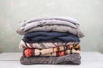Pila di vestiti caldi su commode di legno — Foto stock