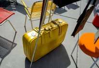 Yellow travel suitcase on floor at chairs in street — Stock Photo