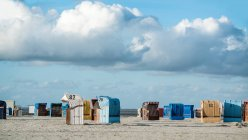 Beach chairs on sandy coastline and clouds in sky — Stock Photo