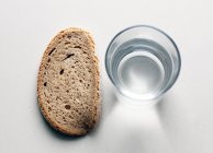 Bread slice and glass of water — Stock Photo