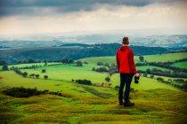 Мандрівник людини в червоний Жакет, стоячи і, тримаючи камеру в горах луг — стокове фото