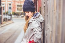 Young woman waiting at wooden fence — Stock Photo